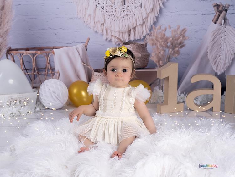 petite fille avec une robe beige en dentelle pose pour une photo