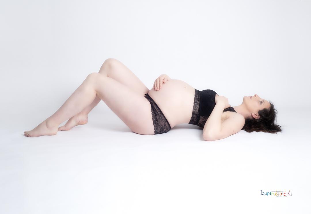 femme enceinte allongée sur le dos fond blanc